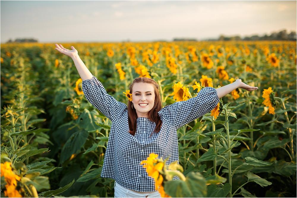 girl senior in sunflower field