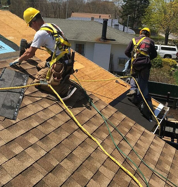 a roofing crew working on a storm damaged roof