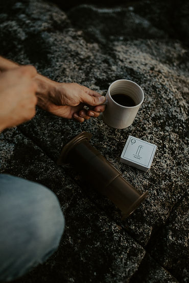 A photo by Pauline Holden of a brewing session on a beach. Hand is holding a coffee cup.