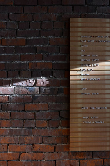 A menu board of a coffee shop on an old brick wall. Button leads to list of wholesale partners