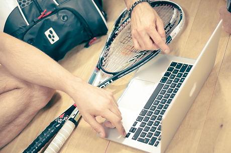 Squash-Schläger und Laptop mit Händen