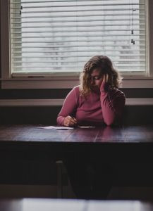 sad girl sitting at a table with pen and paper in hand. infidelity trauma. ian robertson. st catharines ontario