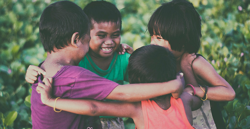 kids group hugging and laughing together. niagara based therapist, ian robertson shares how pain and suffering can be beneficial.