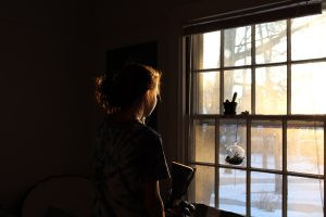 girl looking outside through a window thinking. seek therapy relief with ian robertson located in niagara ontario