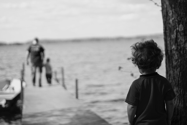 child watching man and child walk along the water. common mistakes parents of blended families make. niagara based counselor ian Robertson discusses