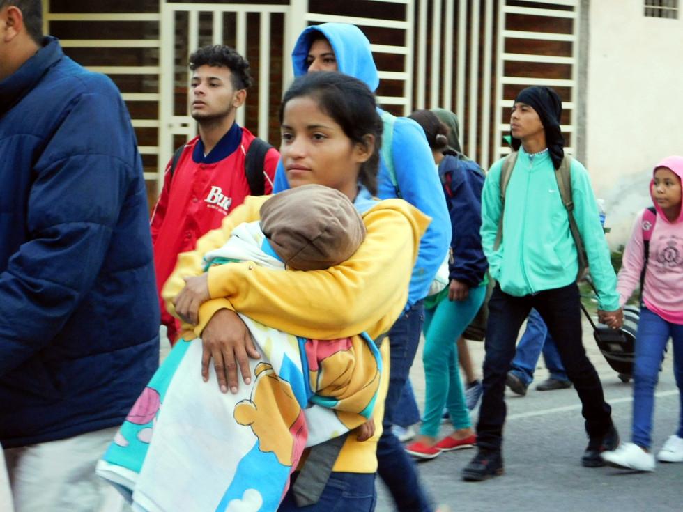 En la fotografía se puede observar a una joven que carga en sus brazos a su bebé, huyendo del desempleo y la desesperanza que se vive en Honduras desde hace muchos años.