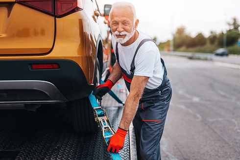 Handsome senior man working in towing service on the road. Roadside assistance concept..jp