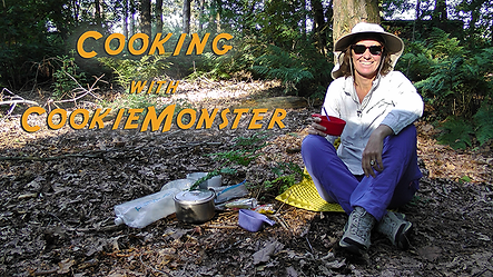 CookieMonster is sitting in a forest against a tree with outdoor back country cooking equipment.