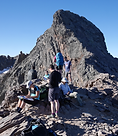 Hikers on tpof a hig mountain pass on the GR20 Corsica