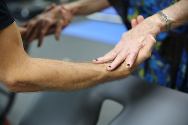 Woman's hands pressing down on PT's hands to build shoulder strength