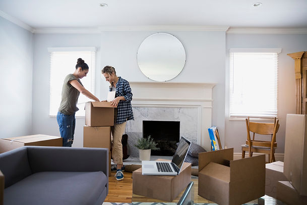 lesbian-couple-unpacking-moving-boxes-in