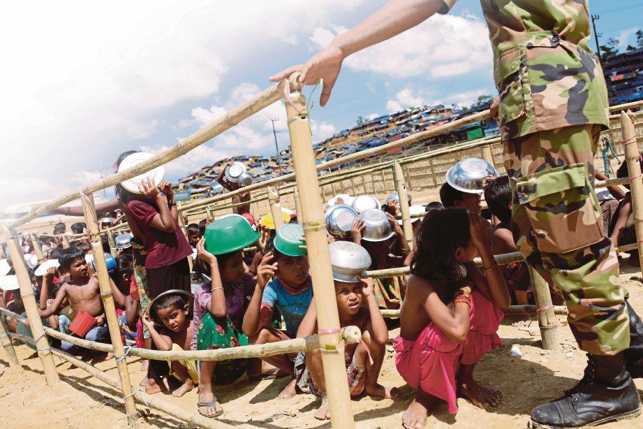Kanak-kanak Rohingya sedang beratur untuk mendapatkan bantuan makanan
