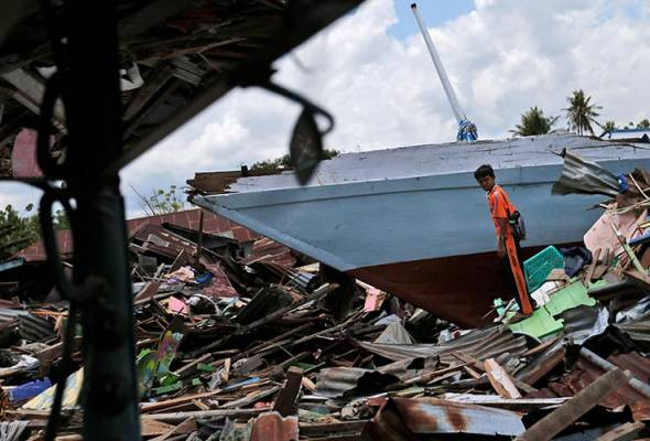 Seorang kanak-kanak melihat keadaan sekitar sebuah bot yang terdampar di atas darat di tengah serpihan kemusnahan akibat tsunami di Kampung Wani, pinggir bandar Palu, Sulawesi Tengah, Indonesia, 10 Okt, 2018. (Foto AP)