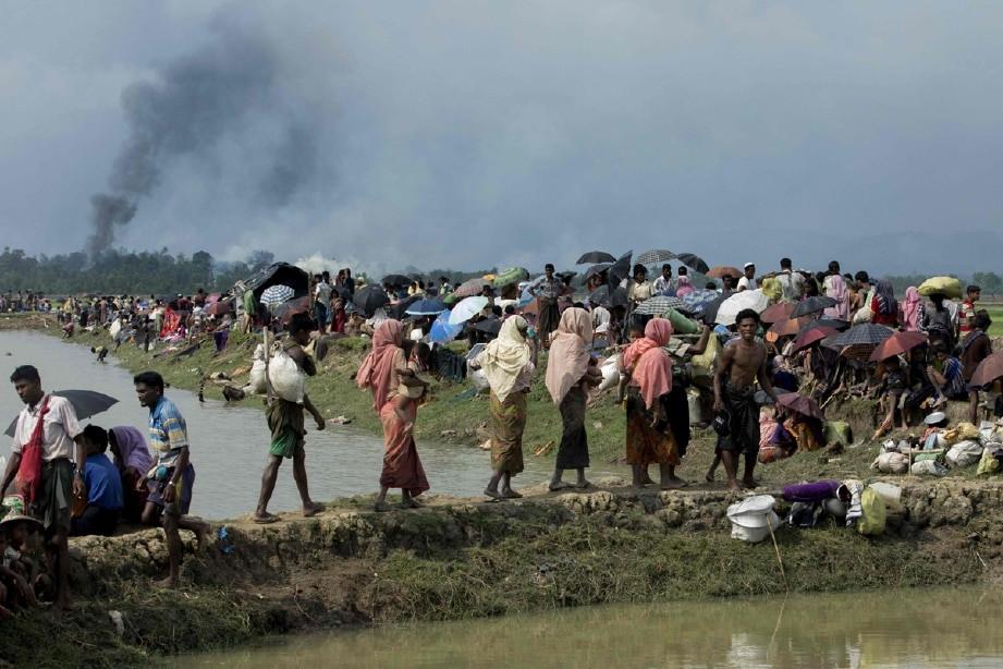 Kepulan asap di bel;akang deretan pelarian dipercayai perkampungan Rohingya yang terbakar di Rakhine, Myanmar
