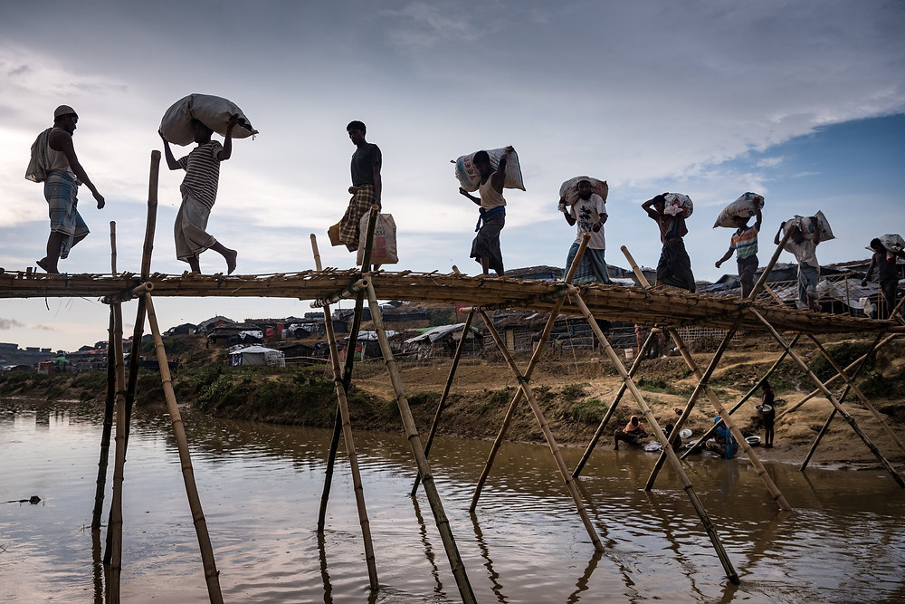Rohingya crossing a makeshift bridge in the Kutupalong refugee camp, outside Cox's Bazar in Bangladesh.