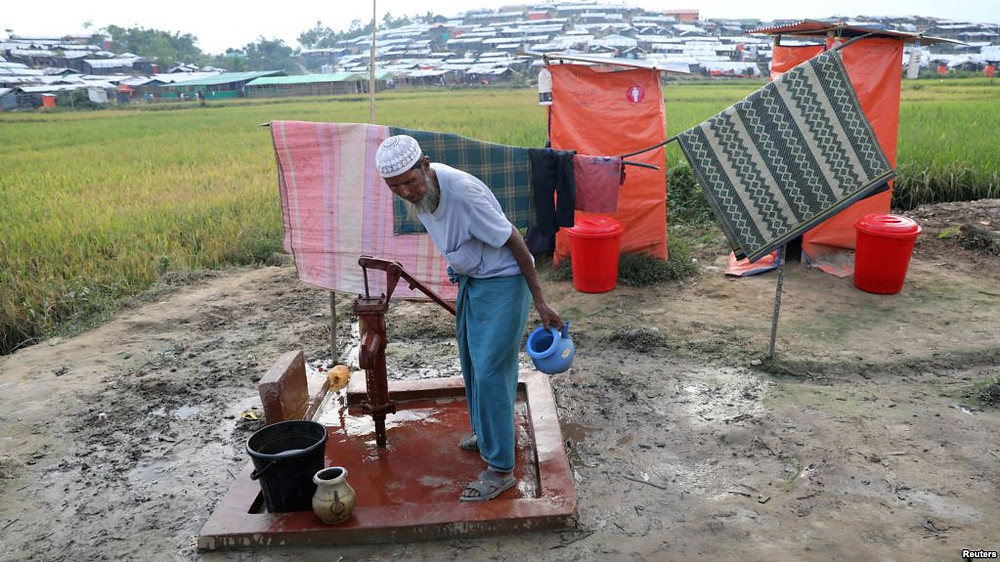 A Rohingya refugee man collects water from a tube-well near to a toilet in Cox's Bazar, Bangladesh, Nov. 15, 2017.