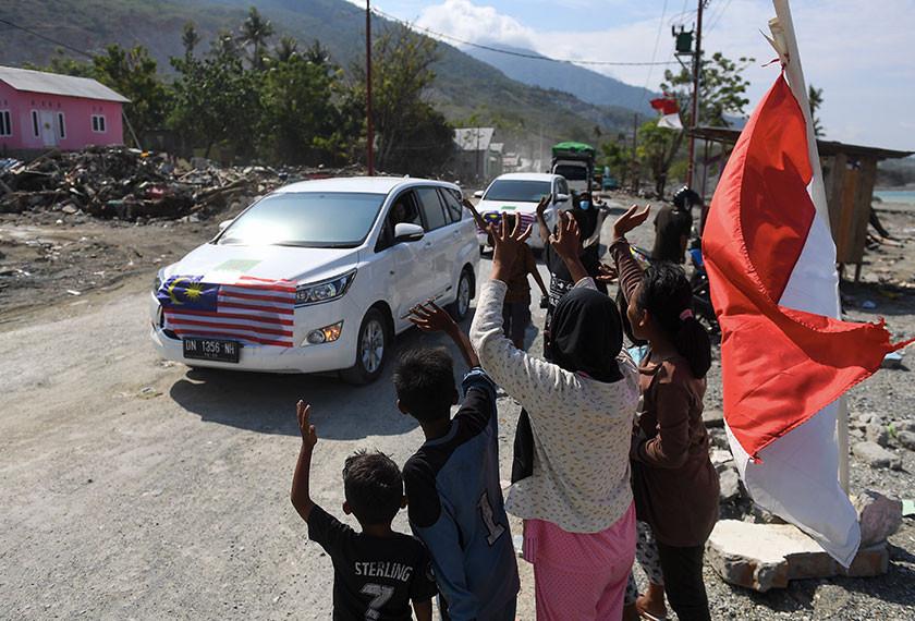 Sebahagian kanak-kanak melambaikan tangan mengucapkan terima kasih kepada konvoi misi kemanusian bencana yang diketuai oleh Majlis Perundingan Pertubuhan Islam Malaysia (MAPIM) di Jalan Malonda Kota Palu hari ini.