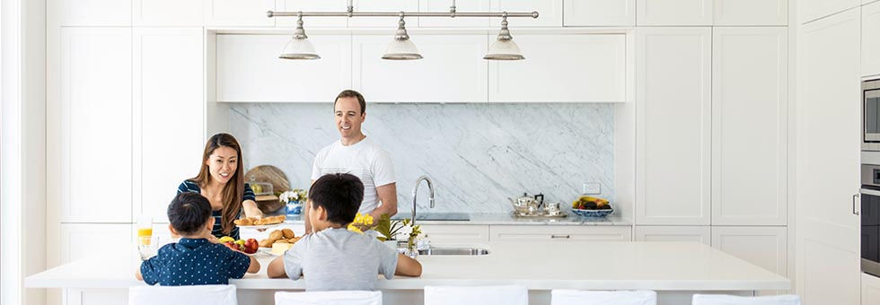 A young family eating breakfast in a moden kitchen featuring new lighting