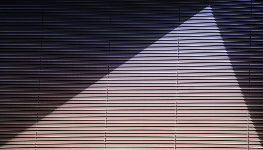 window shutter with a sharp shadow on it