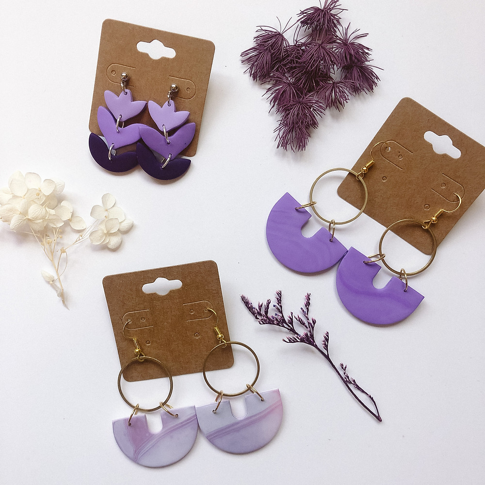 A photo of 3 sets of purple earrings on a white background with dried flowers around them.