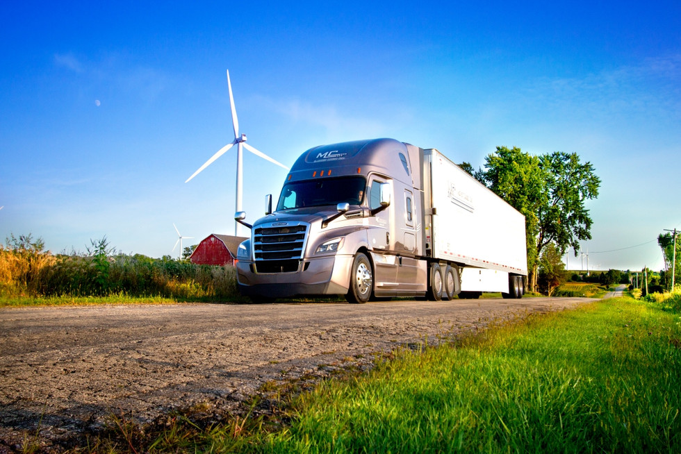 A semi truck and trailer drives down a rural road passed windmills