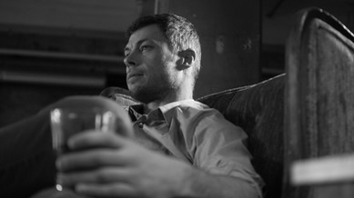 A black and white shot of a man lounging with a glass of whiskey