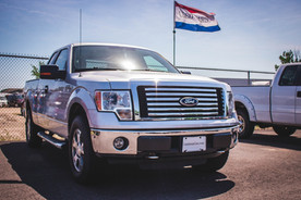A new Ford F-150 sits in a used car dealership lot