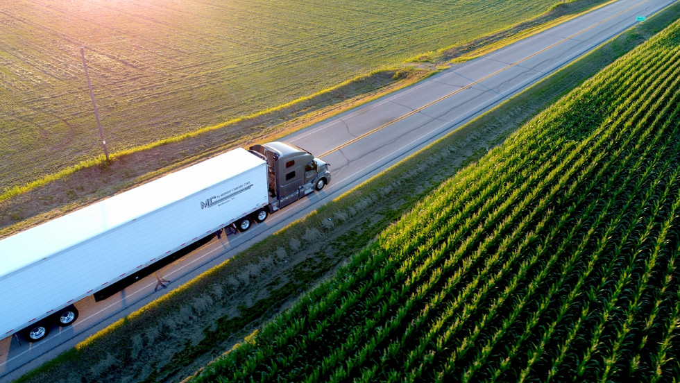 Aerial view of a semi truck driving passed a field at sunset