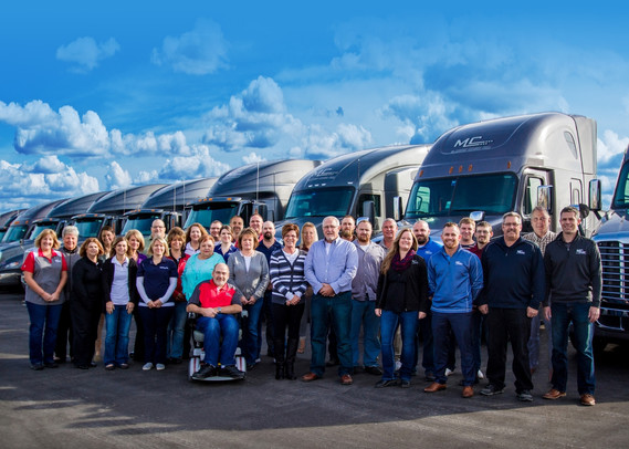 The office employees of a trucking company stand in front of parked semis