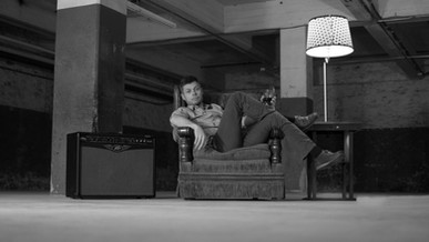 A songwriter sits in a relaxed position in a basement