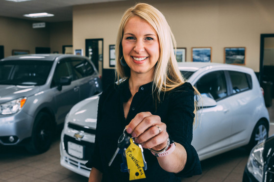 A car saleswoman holds out the keys to a new vehicle