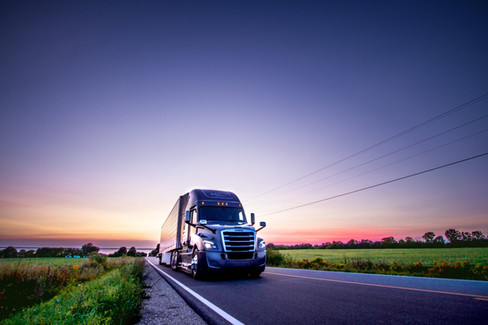 A freightliner semi truck drives down the road at sunset