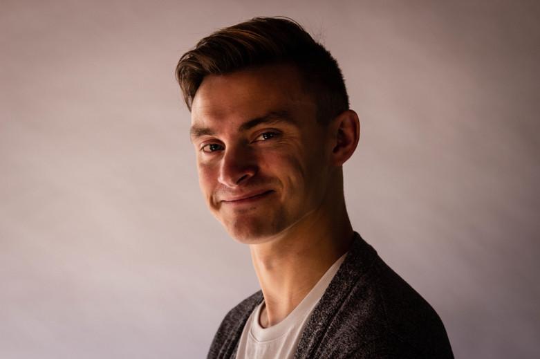A studio headshot of a smiling musician