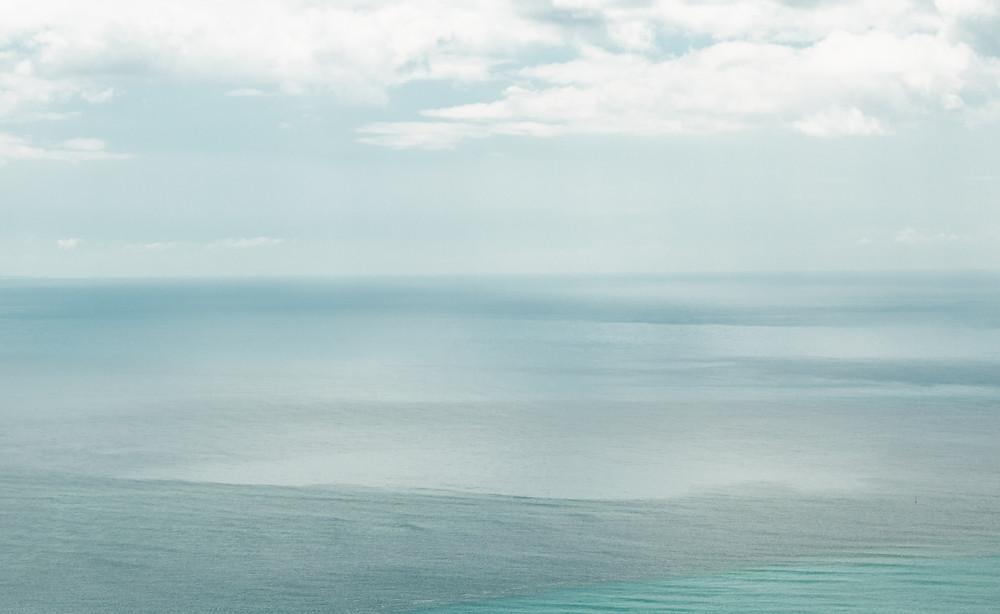 Na parte superior, céu claro com nuvens branca e, na parte inferior, mar com diferente cores.