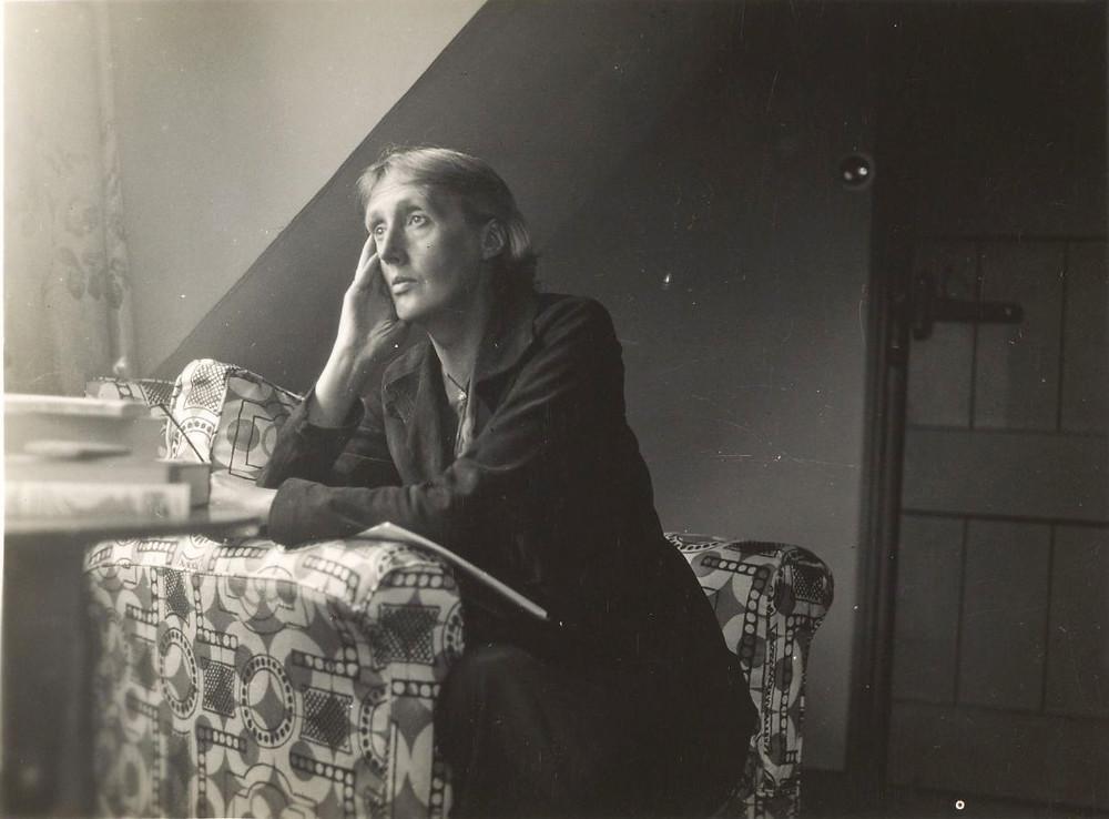 Foto em preto e branco, Virginia Woolf está sentada em uma poltrona larga, olhando para o que parece ser uma janela. O olhar dela parece distante.