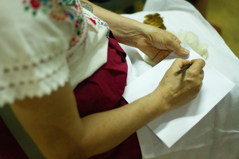Mulher sentada com folha de papel no colo, segurando lápis, escrevendo