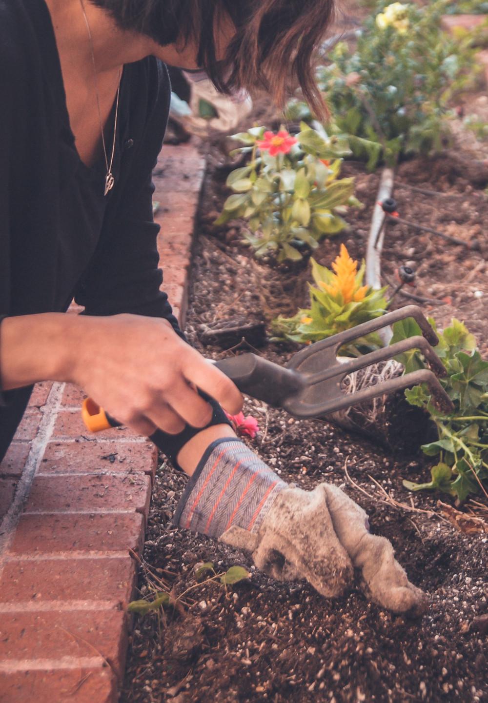 mulher mexendo na terra do jardim