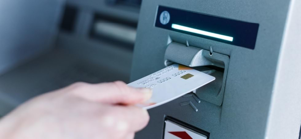 Debit card being put into an ATM.