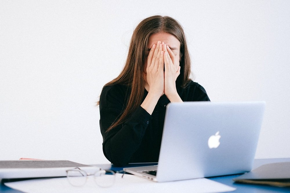 White woman with hands over her face in front of MacBook.