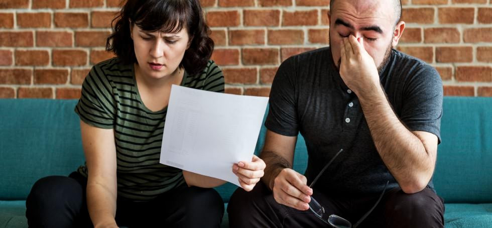 A stressed, anxious couple looking over bills.