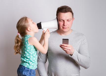 Father using smartphone ignoring his dau