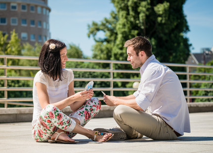 Young couple playing cards outdoor sitti