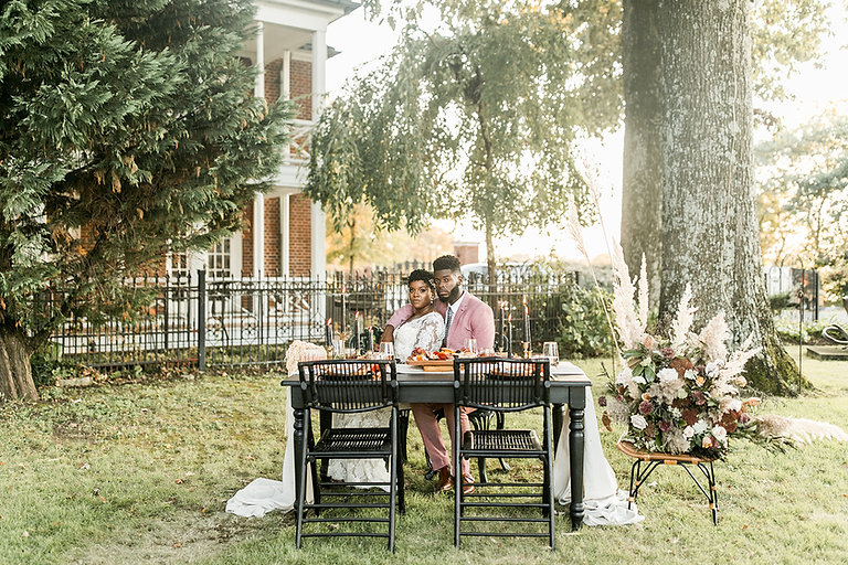 A couple sits at a set table among lush trees in a picturesque setting.