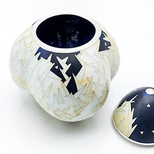 A lidded container by artist Sarah Perkins. The lid is removed, and the vessel has a black interior with a black and white exterior featuring a crystalline design motif reminiscent of shards of ice.