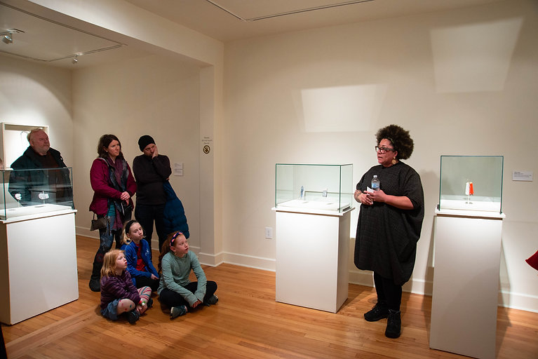 An artist gives a lecture in a gallery to a small group of people.