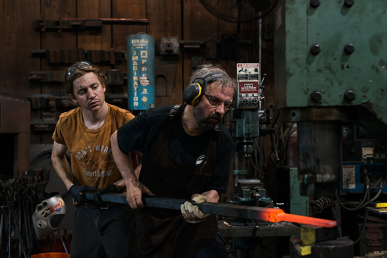 Two blacksmiths hold a glowing hot steel bar under a power hammer.
