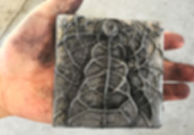 A close-up image of someone holding a handmade aluminum art tile.