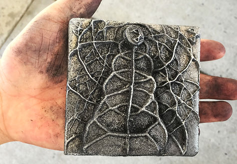 A close-up image of someone holding a handmade cast aluminum art tile.