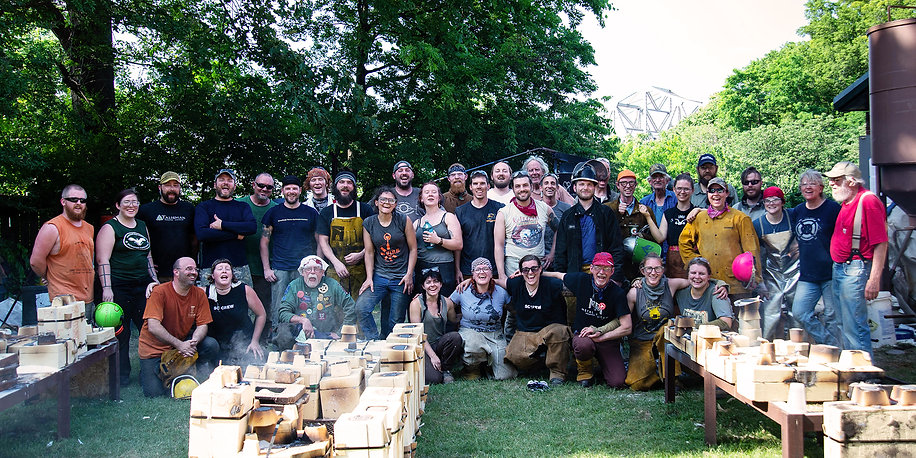 A large group of foundry artists smiling and standing close together after a successful iron pour at the Metal Museum.