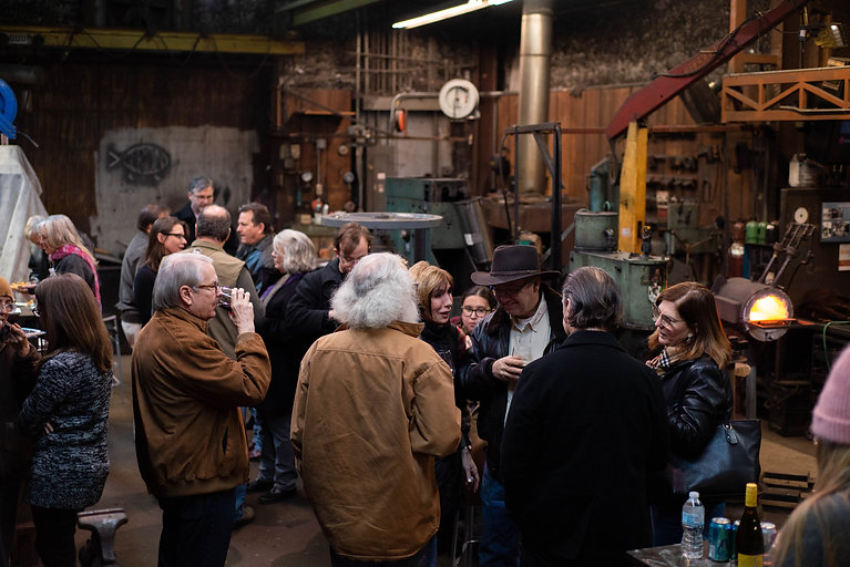 Fire Keepers drinking and eating during a celebration in the Blacksmith Shop.
